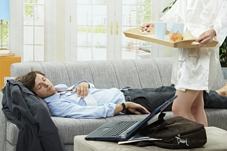 Tired businessman sleeping on couch at home in the morning, his wife bringing breakfast on tray.