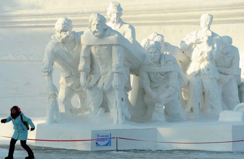 Devushka-poziruet-pered-snezhnoj-skulpturoj-Burlaki-na-Volge-pered-13-festivalem-snega-i-lda-v-Harbine-avtor-Sheng-Li