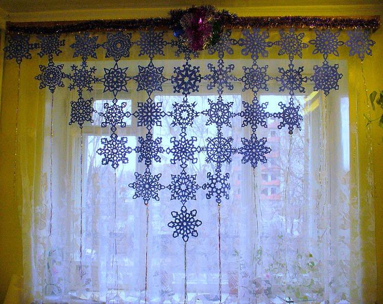 okna-ukrashennye-novogodnimi-vytynankami-na-shtorah