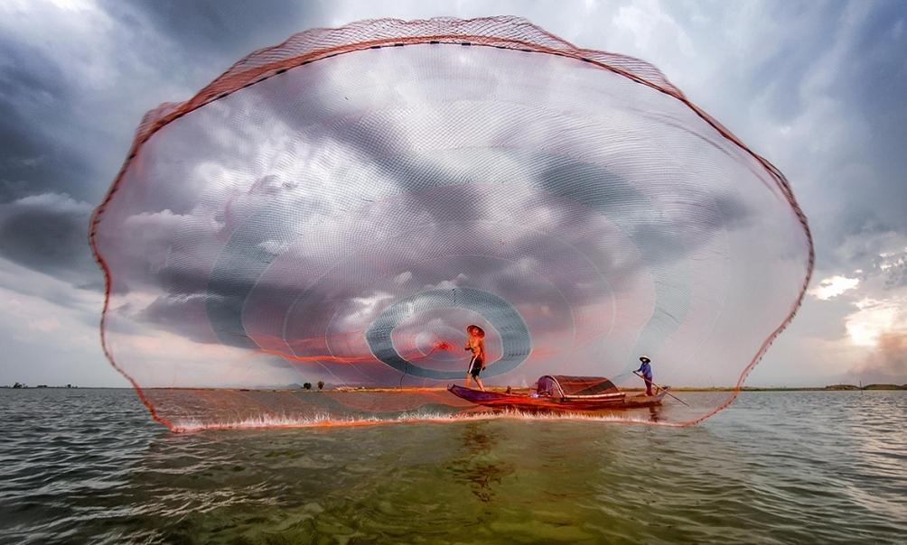 foto-zametki-Vetnam-provintsiya-Kuangbin.-Rybak-zakidyvaet-v-vodu-gigantskuyu-set-pohozhuyu-na-parashyut